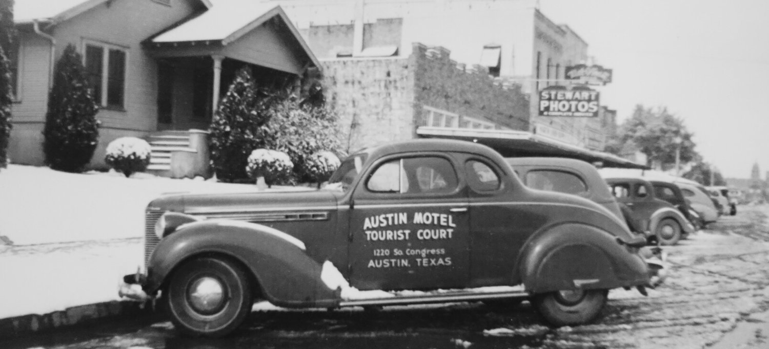 An old black and white photograph of an Austin Motel branded car