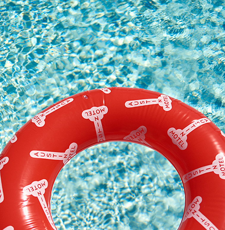 A red Austin Motel branded swim ring floating in a pool