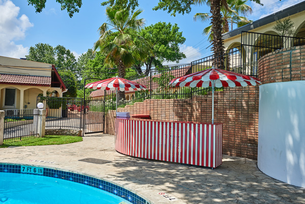 Outdoor poolside bar with red and white striped umbrellas